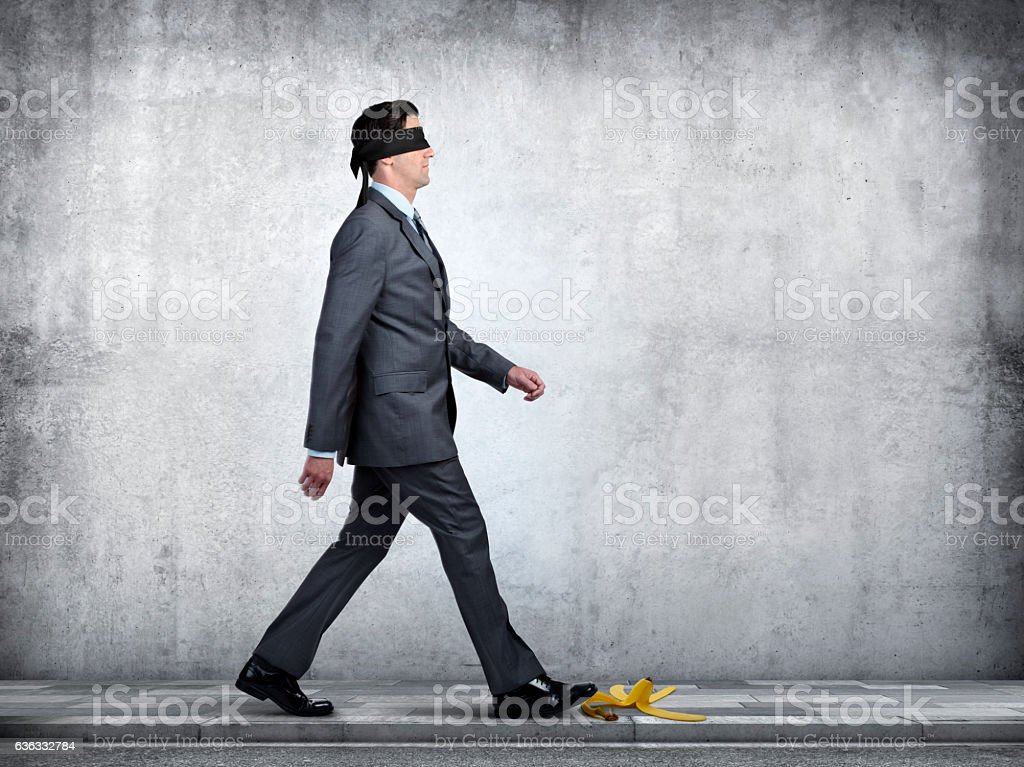 Blindfolded Businessman About To Step On Banan Peel stock photo