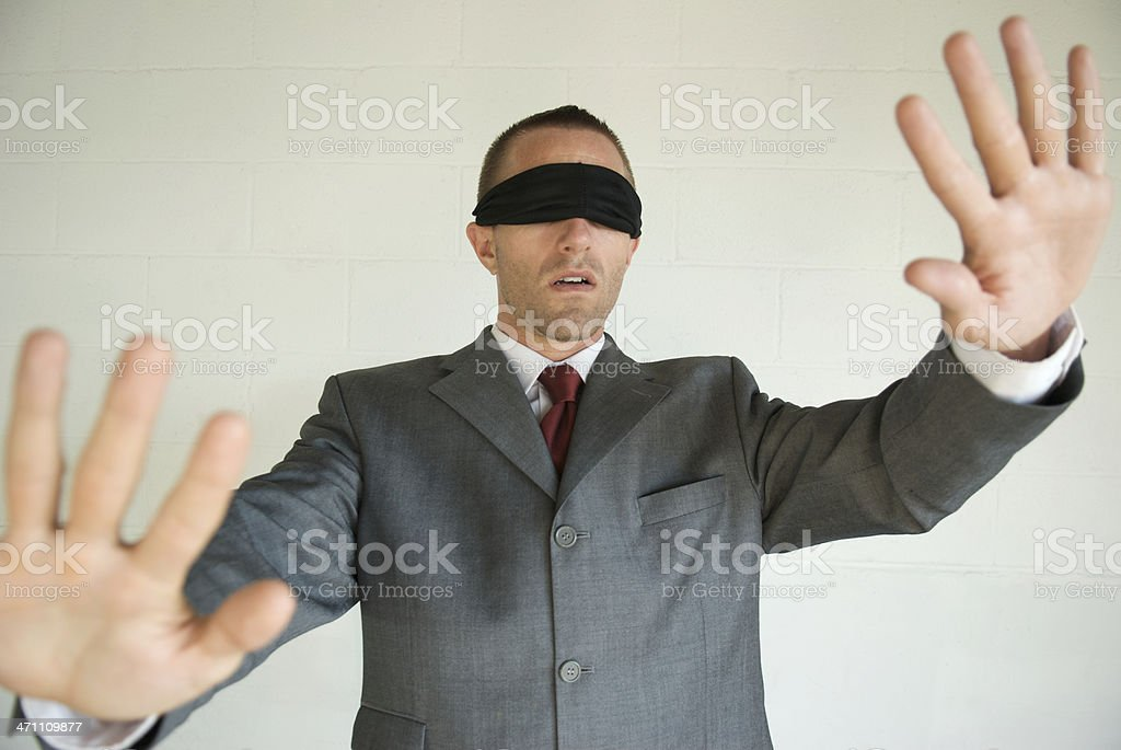 Blindfolded Businessman Blunders Forward With Hands Out stock photo