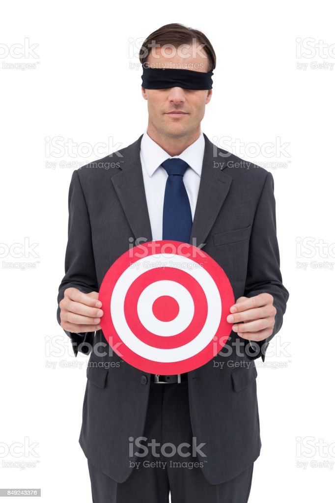 Blindfolded businessman holding a red target stock photo