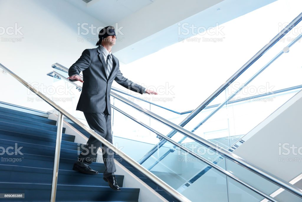 Blindfolded Businessman Navigates Down A Staircase stock photo