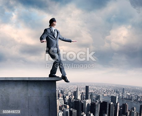 A blindfolded businessman on the ledge of a building high above the city below.
