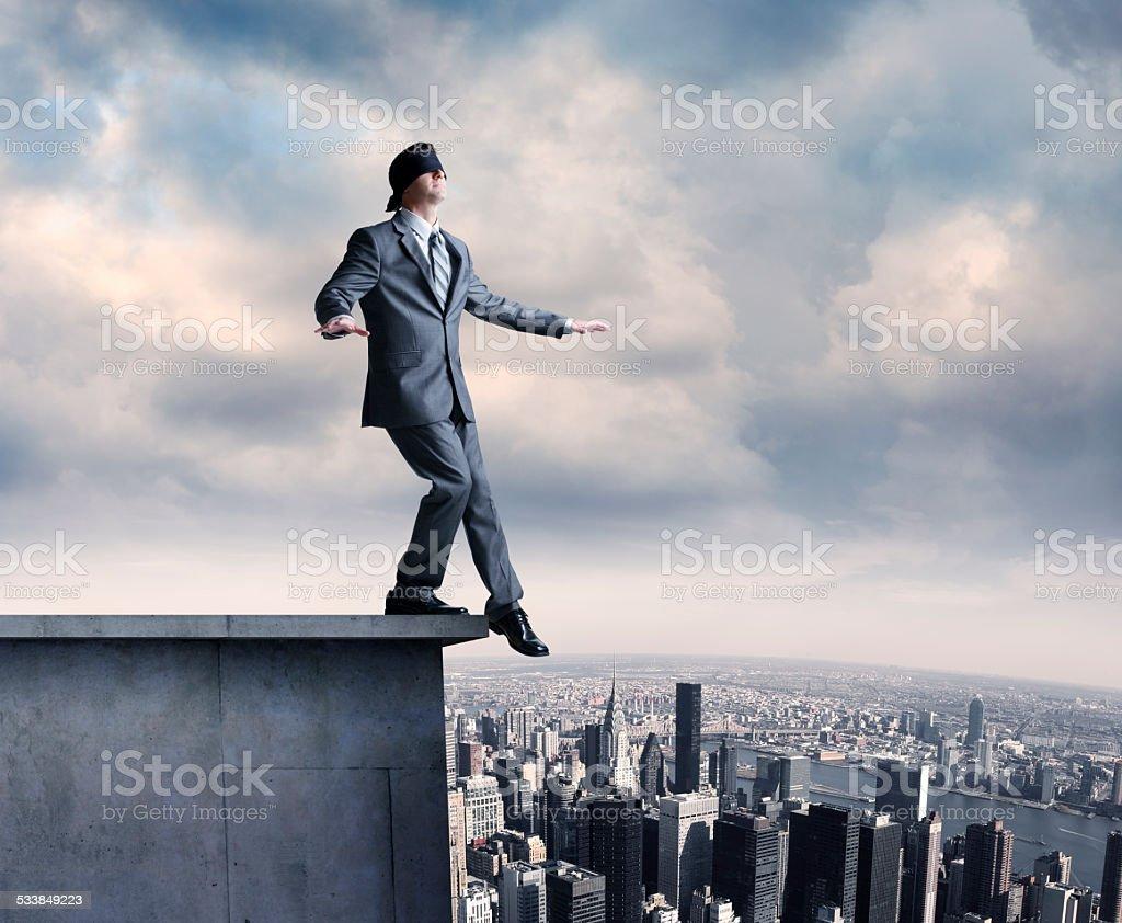 Blindfolded Businessman On Ledge stock photo