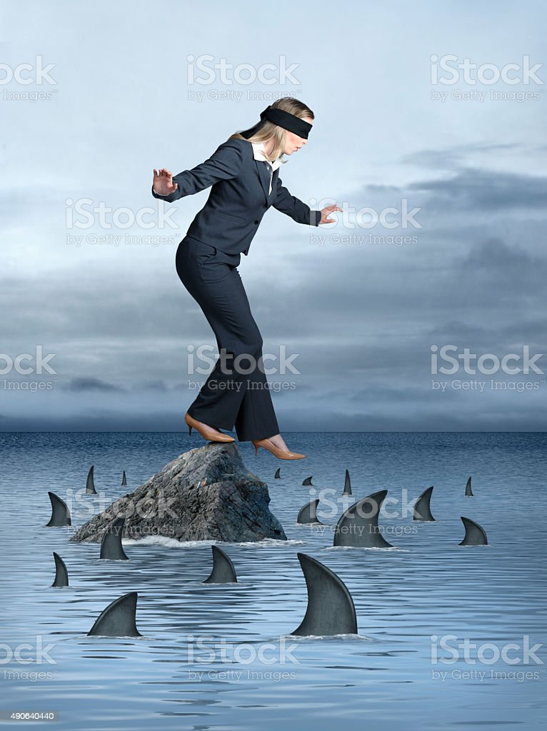 Blindfolded Businesswoman Surrounded by Sharks stock photo