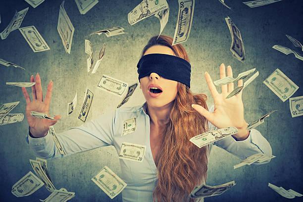 Blindfolded entrepreneur businesswoman trying to catch dollar bills stock photo