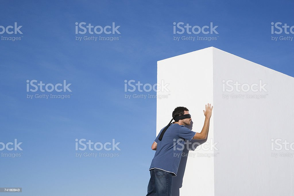 Blindfolded man reaching wall outdoors royalty-free stock photo