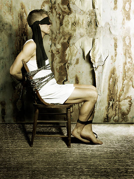 blindfolded hombre sentado en silla - foto de stock
