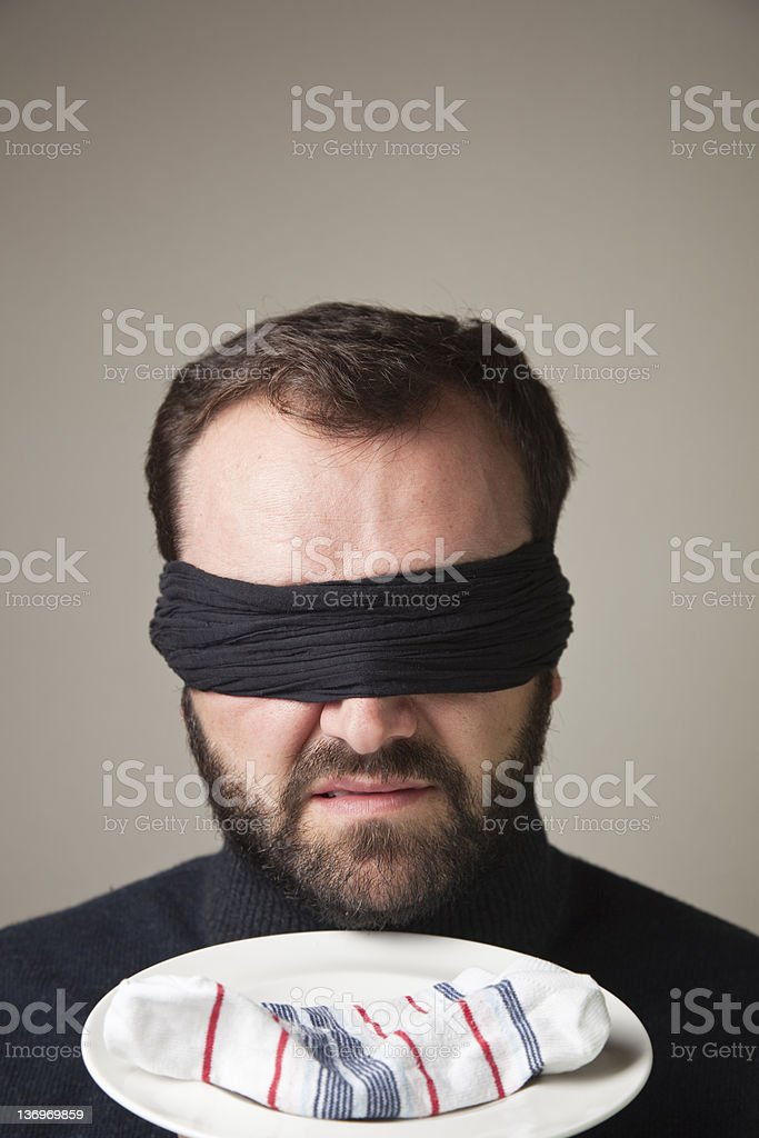 Blindfolded man smelling a dirty sock royalty-free stock photo