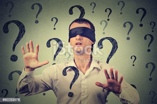 istock blindfolded man stretching his arms out walking through many question marks 692253576