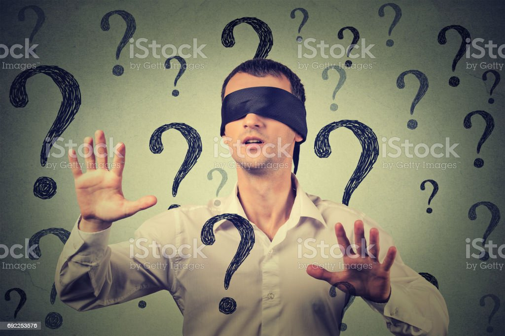 blindfolded man stretching his arms out walking through many question marks stock photo