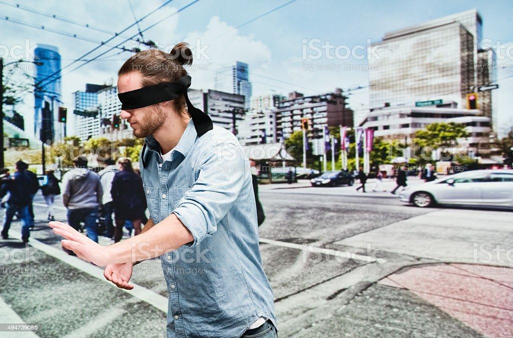Blindfolded man walking on road stock photo