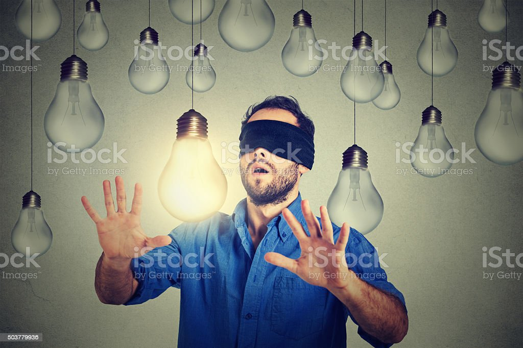 Blindfolded man walking through lightbulbs searching bright idea stock photo