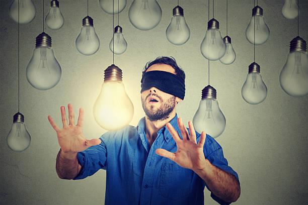 Blindfolded man walking through lightbulbs searching bright idea stock photo