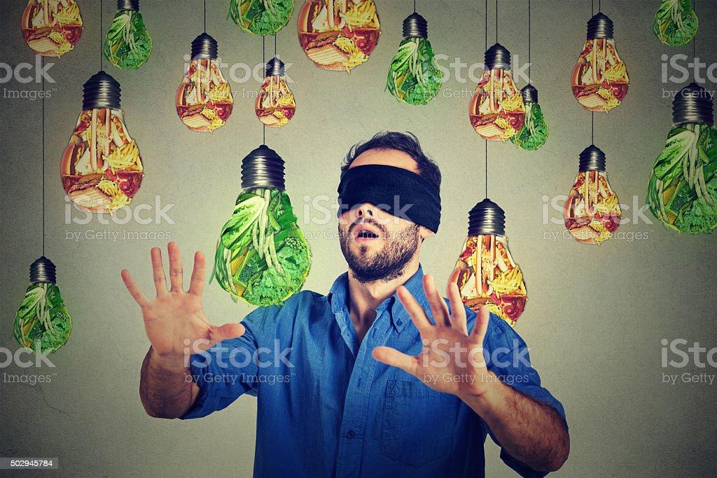 Blindfolded man walking through lightbulbs shaped junk food vegetables stock photo