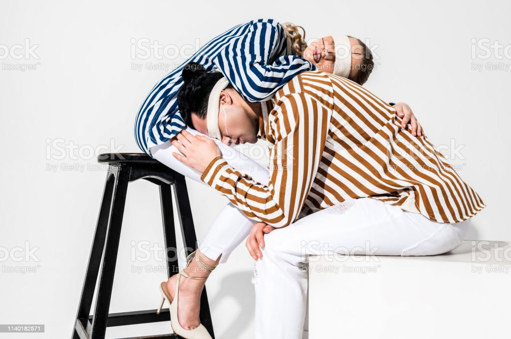 Creative pose. Blindfolded professional models wearing white trousers...