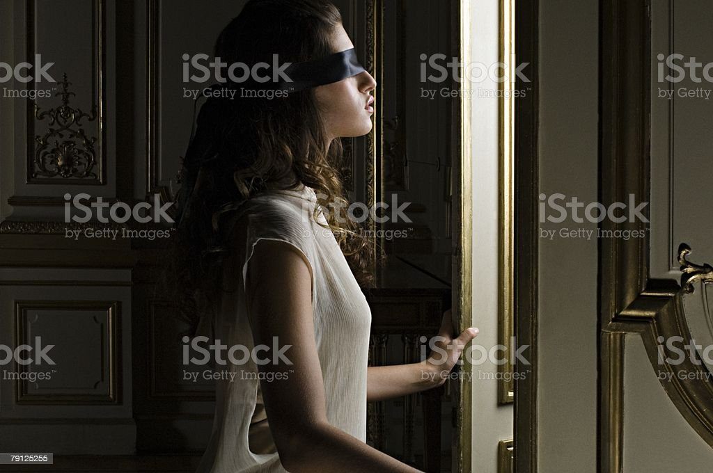 Blindfolded woman opening door 免版稅 stock photo