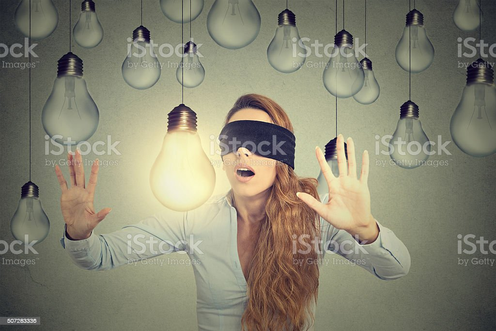 Blindfolded woman walking through lightbulbs searching bright idea royalty-free stock photo