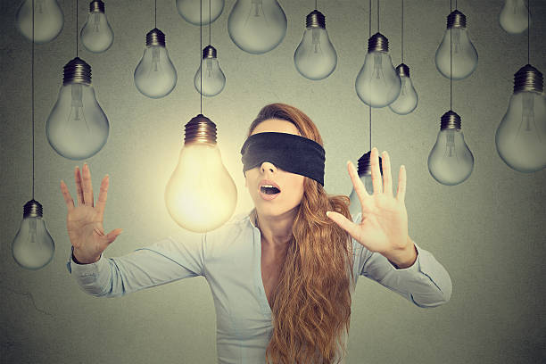 Blindfolded woman walking through lightbulbs searching bright idea stock photo