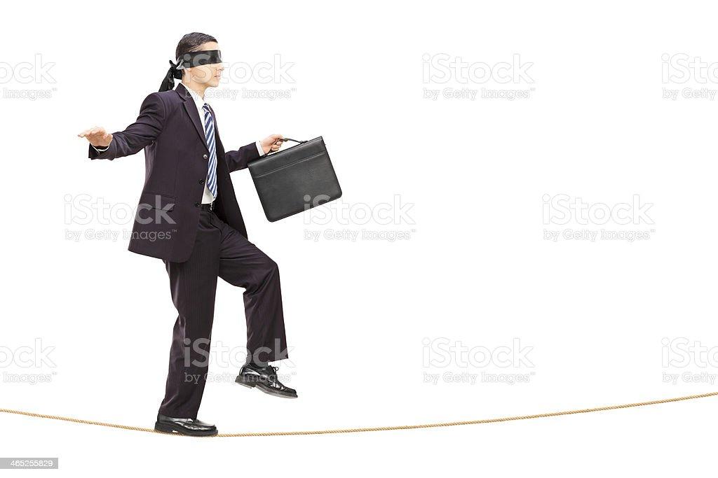 Blindfolded young businessman walking on rope stock photo