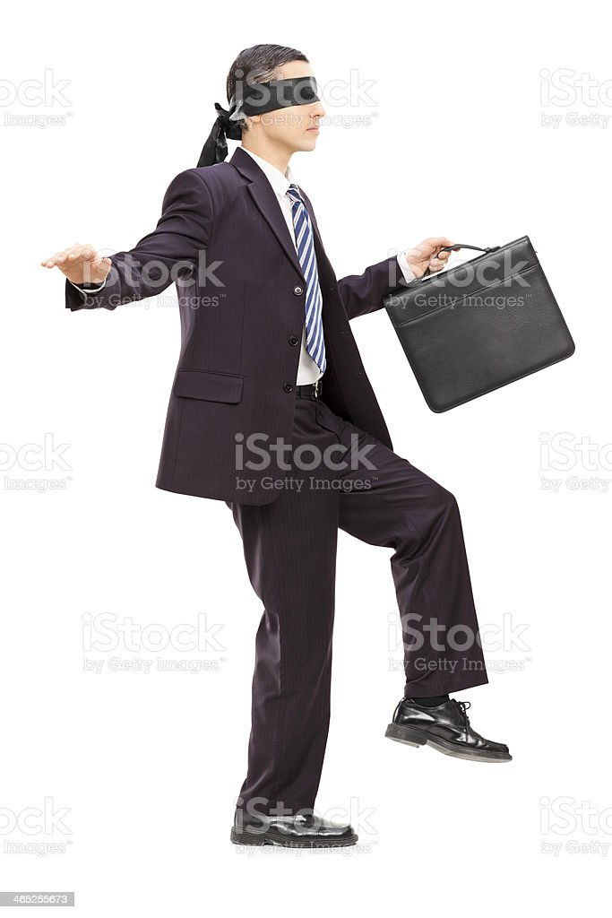 Blindfolded young businessman with briefcase walking stock photo