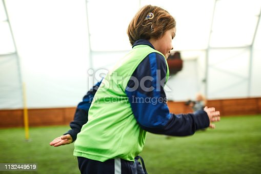 Group of children on soccer training. Focus on boy with cochlear implant