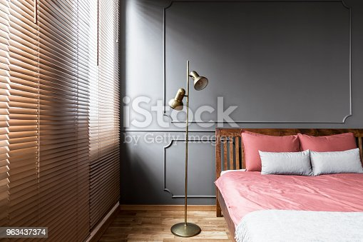 istock Blinds and golden lamp in dark and elegant bedroom interior with pink sheets on a wooden bed and molding on the wall. Real photo 963437374