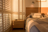 Beautiful golden light filtering through shutters in bedroom.