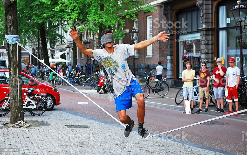 Blinfolded man walking on a tightrope stock photo