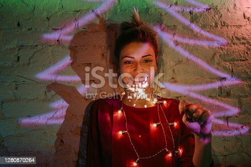 Portrait of a young smiling woman holding sparklers under the neon lights; celebrating Christmas and upcoming holidays alone in her apartment.