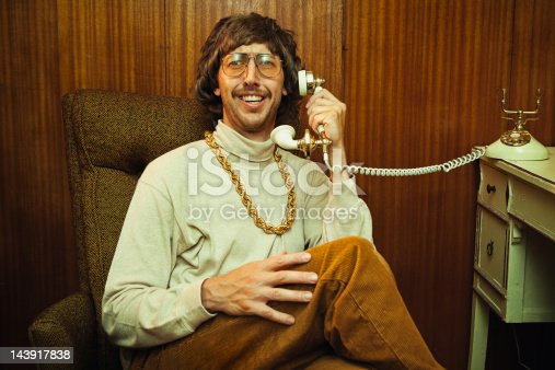 A smiling goofy man from the 1970s - 1980s relaxes as he talks on his vintage rotary telephone. He's wearing a turtleneck, high waisted elastic corduroy pants, and his fancy gold chain necklace .  Classy tinted glasses and suave mustache.  Wood panel wall in the background.