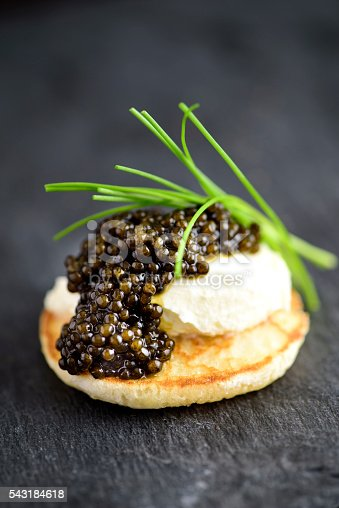 Blini with Sour Cream and Real Black Caviar Close-up