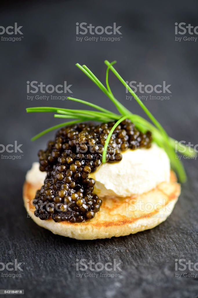 Blini with Sour Cream and Real Black Caviar stock photo