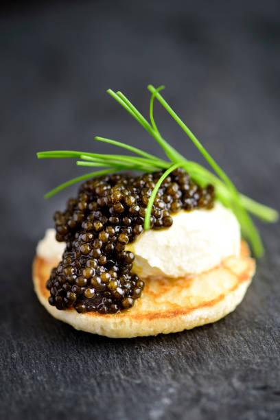blini con crema agria y negro real caviar - caviar fotografías e imágenes de stock