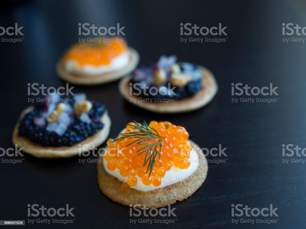 Blinis with fish eggs as appetizer stock photo