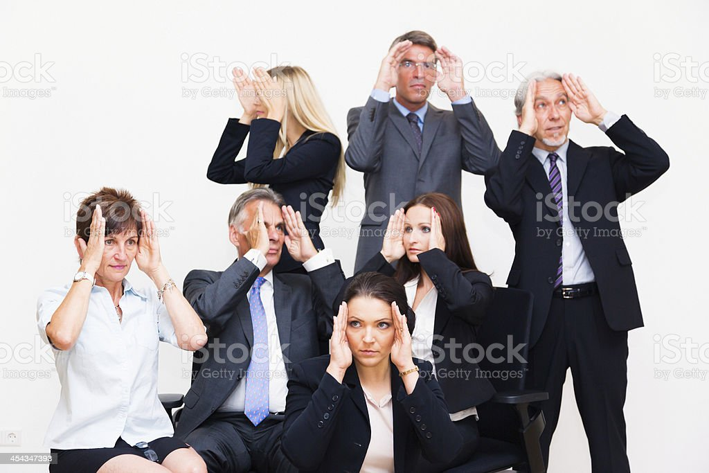 blinkered business team looking in different directions stock photo