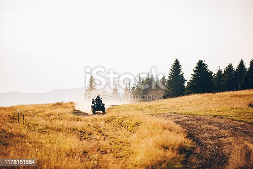 Couple riding on a quad-bike together on a mountain peak somewhere in serbia