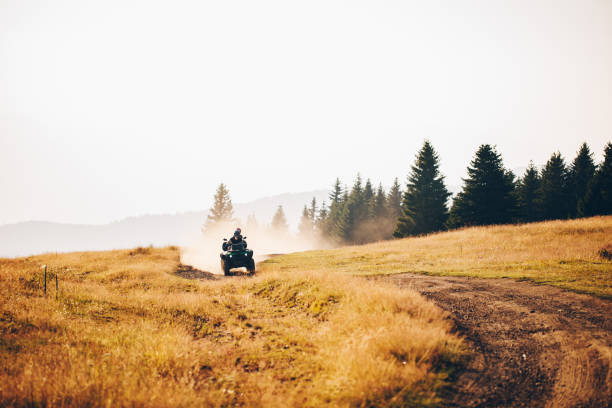Blissful exploration Couple riding on a quad-bike together on a mountain peak somewhere in serbia quadbike stock pictures, royalty-free photos & images