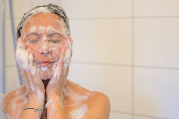 Blissful middle-aged woman enjoying a shower stock photo