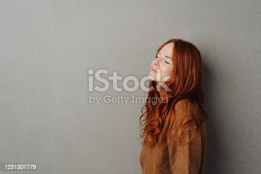 Blissful serene young woman with closed eyes tilting her head back with a quiet smile of pleasure as she takes a moment to relax over a grey studio background with copy space