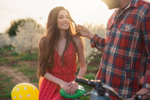 Blissful Smile When He's Close To Her Unrecognizable young man flirting and touching hair of his beautiful girlfriend sitting on the bicycle with balloons, in the orchard full of trees in bloom. sun shining through dresses stock pictures, royalty-free photos & images