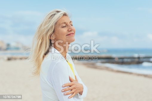 Blissful woman standing on a beach smiling with folded arms and eyes closed as she relaxes