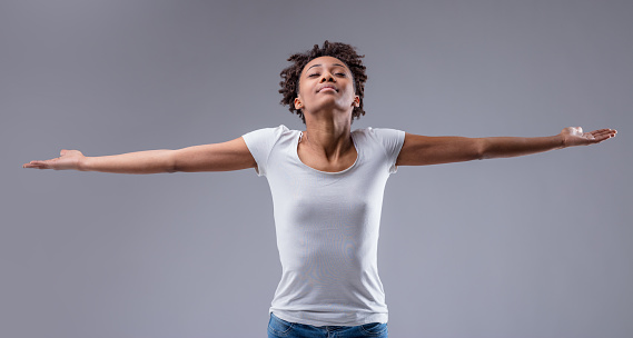 Blissful young woman celebrating the peace and tranquility relaxing with outstretched arms, eyes closed and a serene smile on a grey studio background with copyspace