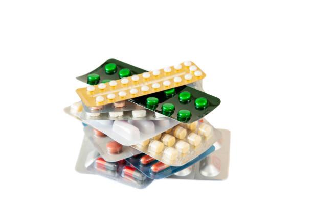 Blisterpackungen mit runden mehrfarbigen Tabletten auf weißem Hintergrund isoliert. – Foto