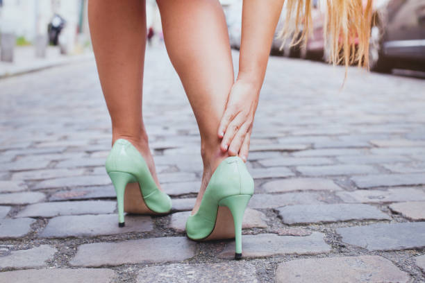 blisters, woman on high heels has difficulties to walk - human foot stock photos and pictures