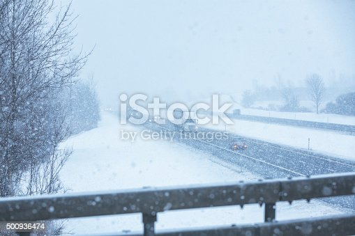 1127834626 istock photo Blizzard Snow Storm Traffic From Overpass Above Expressway 500936474