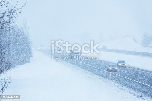 1127834626 istock photo Blizzard Snow Storm Traffic on Slippery Winter Expressway 500936556