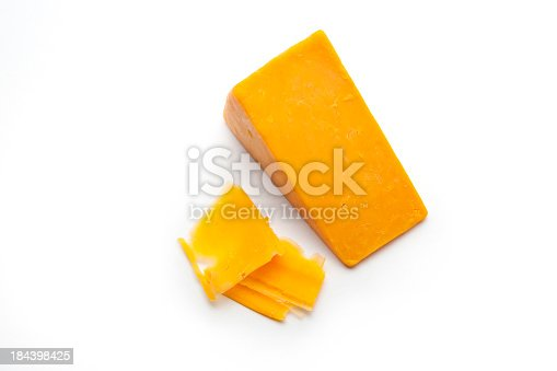 A block and some shaved slices of cheddar cheese on a white studio background.