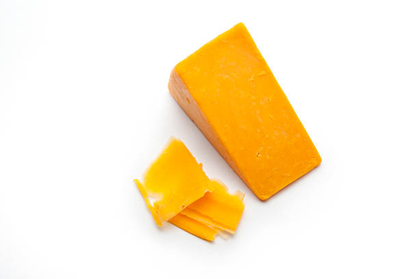 Block and Shavings of Cheddar Cheese A block and some shaved slices of cheddar cheese on a white studio background.   cheddar cheese stock pictures, royalty-free photos & images