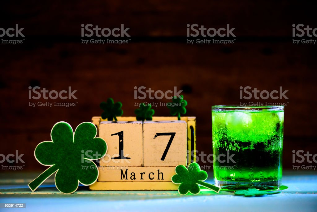 Block calendar for St Patrick's Day, March 17, with green clover leaf, green water and gold bitcoin on bright green Mulberry paper background stock photo