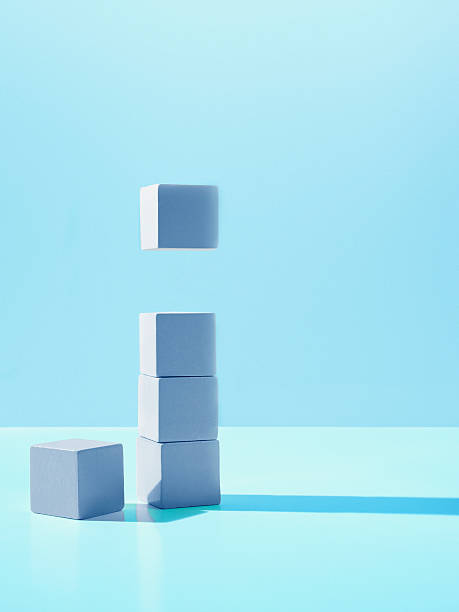Block hovering over stack of blocks stock photo