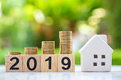 istock 2019 Block number and house model on stack coins. 1063268656